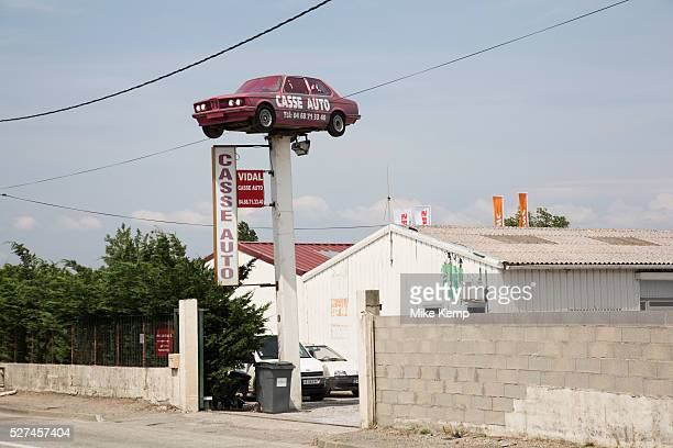 BMW car raised high above a Casse Auto repair shop in Carcassonne LanguedocRoussillon France