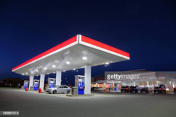 car refueling at gas station during the night - convenience store stock photos and pictures