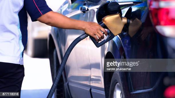 car refueling on a petrol station and employees filling . - gas tank stock photos and pictures