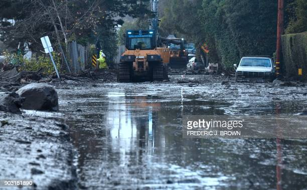 A car remains stuck in the mud as a cleanup crew work to clear mud beside a closed off section of US Hwy 101 flooded after mud and debris broke...