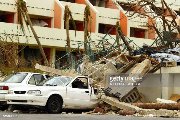 A car remains under rubble 23 October in the hotel area in Cancun after the city was hit by Hurricane Wilma Although heavy rains had subsided as the...