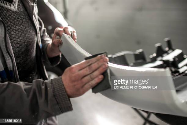 car repair technician using a sanding paper to remove excess filling form a car bumper that got damaged in accident - bumper stock pictures, royalty-free photos & images