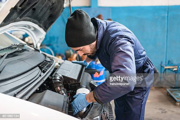 car repairman fixing the truck engine on the garage