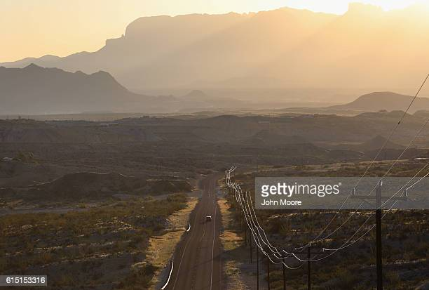 A car rides down open road after sunrise on October 16 2016 in the Big Bend region of west Texas near Terlingua Texas The rugged vast and remote...