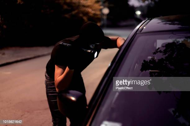 car robber with flashlight - vandalism stock pictures, royalty-free photos & images