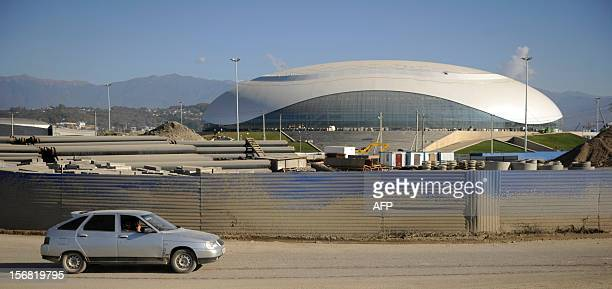 A car rolls near the Bolshoi Ice Palace construction site at the Olympic Park in the Russian Black Sea resort of Sochi on November 22 2012 Sochi will...