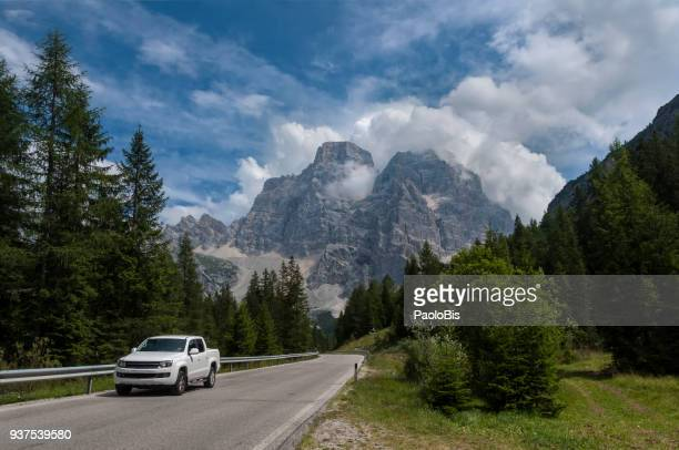 A car runs on a road below Monte Pelmo in the Dolomites, Veneto, Italy
