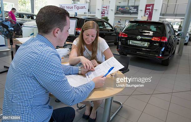 Car sales conversation between a seller and a customer female in a Volkswagen car dealer in Bonn