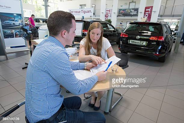 Car sales conversation between a seller and a customer female in a Volkswagen car dealer in Bonn