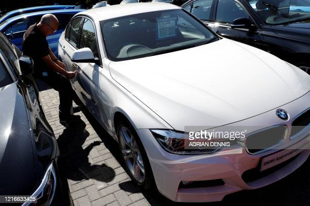 Car sales driver Gary Lee applies a sticker alerting customers not to enter a vehicle if the sticker's seal is broken, due to it having been cleaned...