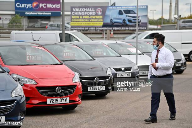 Car sales person wearing PPE including a face mask and gloves as a precautionary measure against COVID-19, walks past vechiles parked on the...