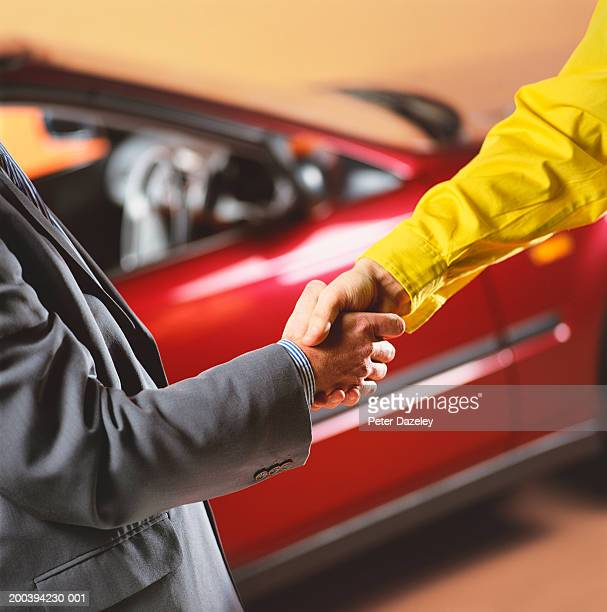Car salesman and male customer shaking hands by car, close-up