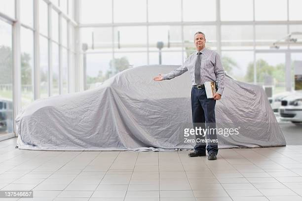 car salesman displaying car under cloth - car dealership stock pictures, royalty-free photos & images