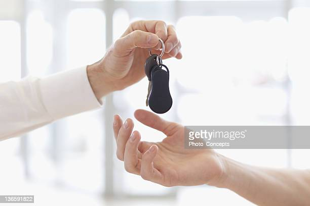 car salesman handing keys to customer - human limb stock pictures, royalty-free photos & images