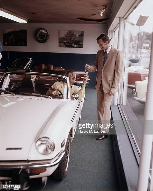 Car Salesman Handing Over Key For New Car To Businessman