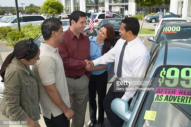 Car salesman selling car to family, shaking man's hand, smiling