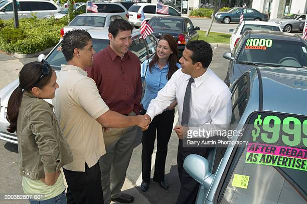 Car salesman selling car to family, shaking young man's hand, smiling