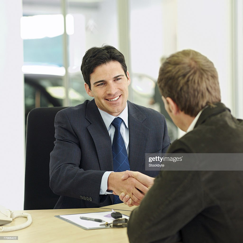 Car salesman shaking hands over desk with customer in car showroom : Stock Photo