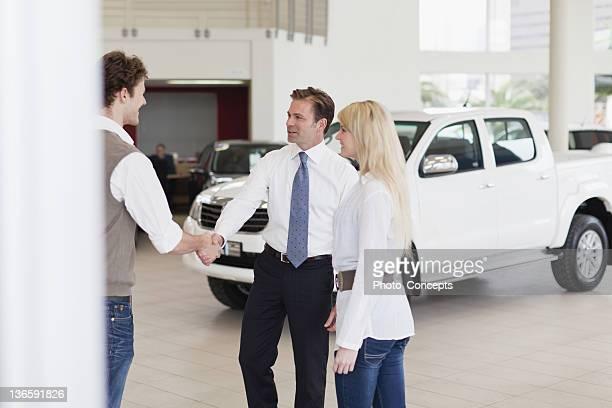 車のセールスマンとして働く顧客の手を振る