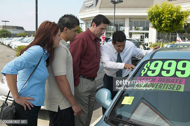 Car salesman showing car to couple with adult son, outdoors
