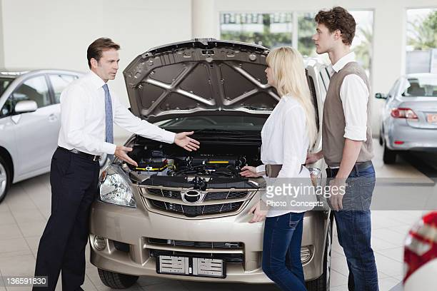 car salesman showing engine to customers - explaining stock pictures, royalty-free photos & images