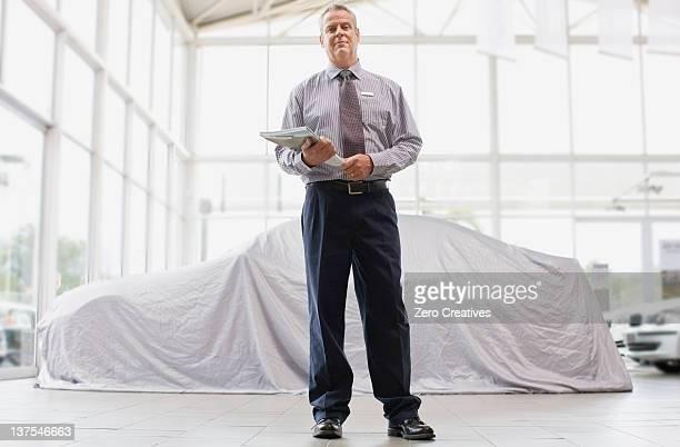 Car salesman standing in showroom