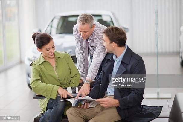 Car salesman talking with couple