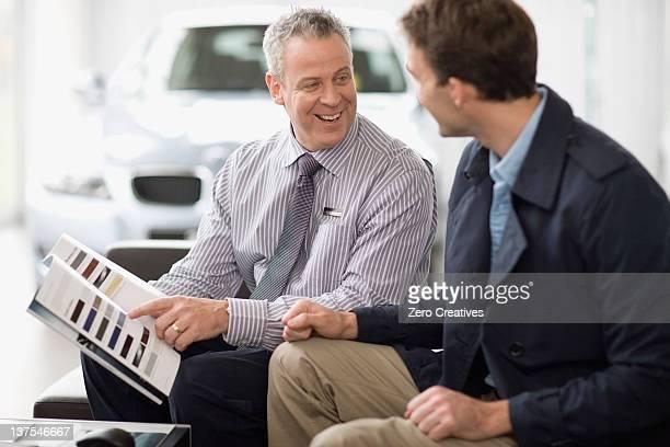 Vendeur voiture de parler avec le client