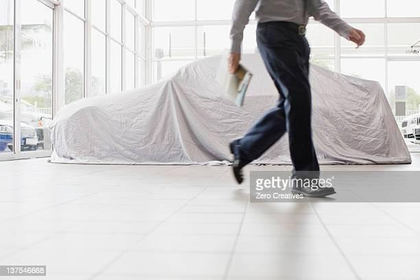 Car salesman walking in showroom
