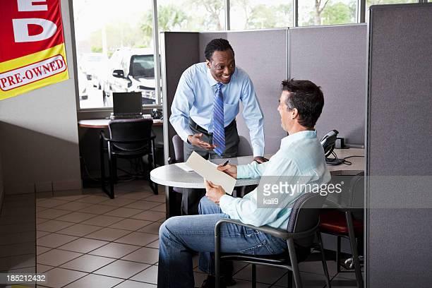 Vendedor de coches con el cliente