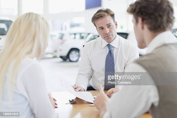 car salesman with customers at desk - car salesperson stock pictures, royalty-free photos & images