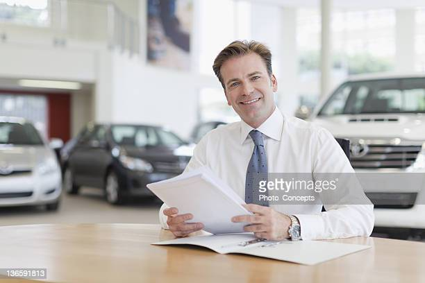 car salesman with paperwork at desk - car salesperson stock pictures, royalty-free photos & images