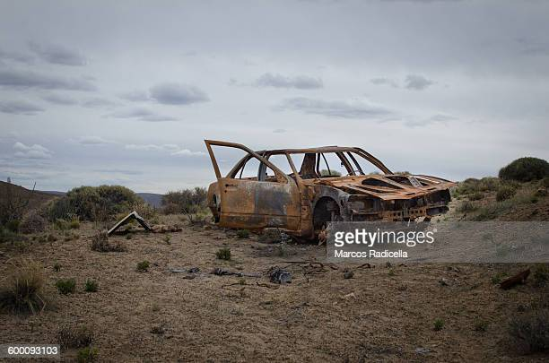 car scrap in the middle of nowhere - abandoned car stock photos and pictures