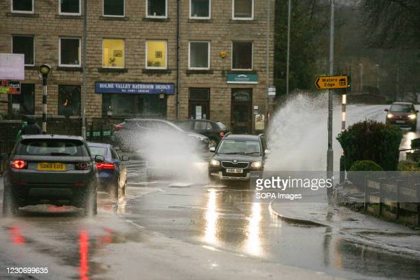 Car seen splashing water as it moves on a waterlogged street during a heavy rainfall in Holmfirth. Parts of the UK including South Yorkshire and...