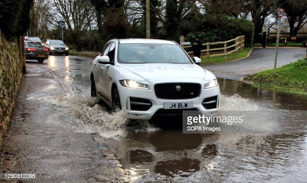 Car seen splashing water as it moves on a waterlogged street. Widespread flooding in Bedford and surrounding villages, where the River Great Ouse has...