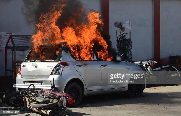 Car set alight by angry lawyers outside the district court after a police inspector shot a lawyer in the court premises on March 11 2015 in Allahabad...