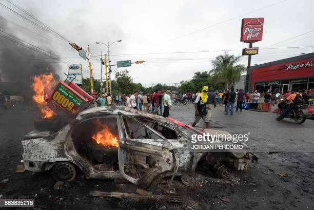A car set on fire by supporters of Honduran presidential candidate for the Opposition Alliance against the Dictatorship coalition Salvador Nasralla...