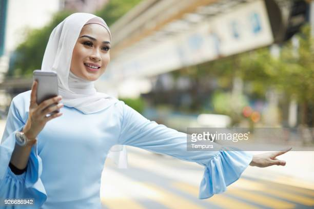 Car sharing, hailing a taxi in Kuala Lumpur.