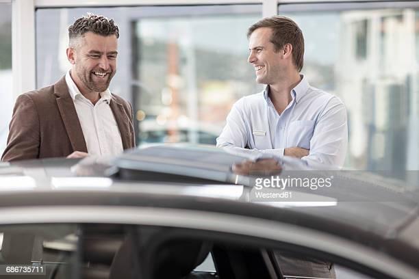 Car showing car to happy customer at car dealership