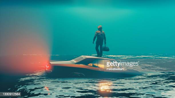 car sinks into water while driver escapes and stands on the roof - extreme weather stock pictures, royalty-free photos & images