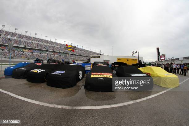MENCS car sit under cover because of inclement weather prior to the Coke Zero 400 NASCAR Monster Energy Series qualifying at Daytona Beach Florida