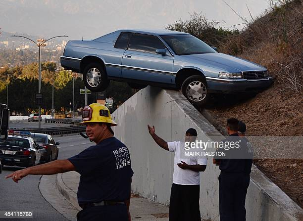 A car sits atop an embankment after losing control and skidding up the concrete retaining wall on South La Brea Ave in Baldwin Hills Los Angeles on...
