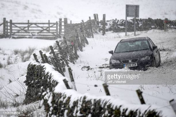 A car sits in a ditch following heavy snow on the A702 Dalveen pass where on Tuesday evening Moffat mountain rescue team helped twelve people to...