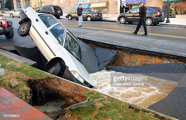 A car sits in a sinkhole caused by a broken water main which collapsed part of Friendship Blvd on December 3 2010 in Chevy Chase Maryland No one was...