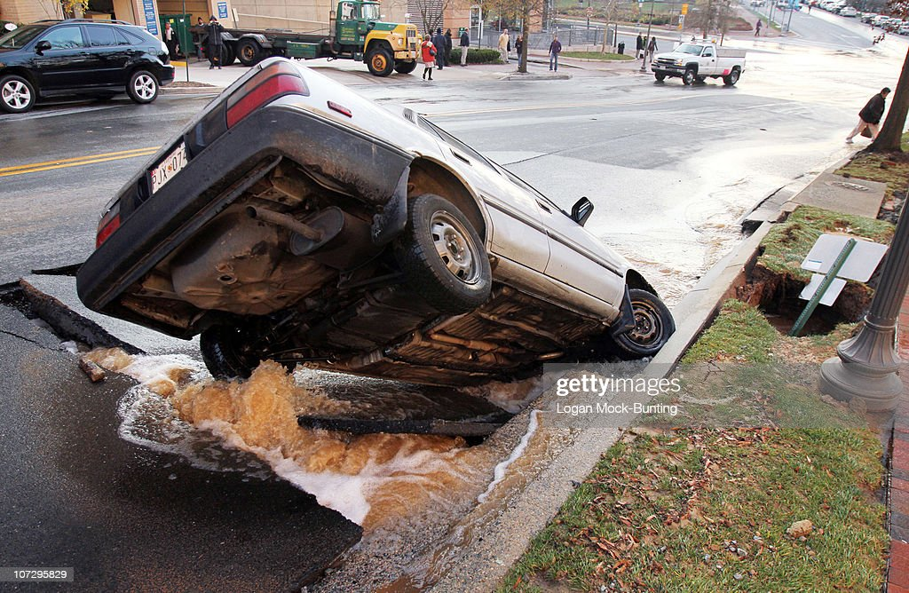 A car sits in a sinkhole caused by a broken water main