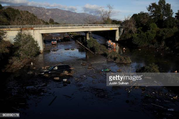 A car sits in mud and debris on a flooded section of Highway 101 after a mudslide on January 10 2018 in Montecito California 17 people have died and...