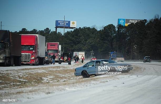 A car sits in the median along Interstate 75 in icy conditions January 29 2014 in Atlanta Georgia Thousands of motorists were stranded many overnight...
