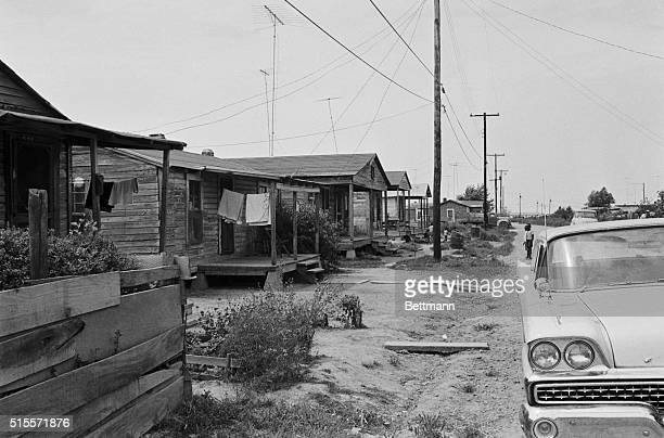 A car sits on the road in front of wooden shacks on Lady Bird Avenue The houses have outhouses and share a communal water pump Belzoni Mississippi...