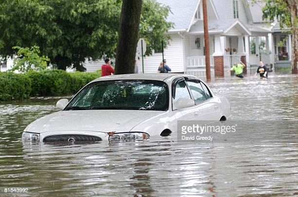 Car sits partially submerged as people try to rescue items from their home on June 12, 2008 in Cedar Rapids, Iowa. Much of the city has been...