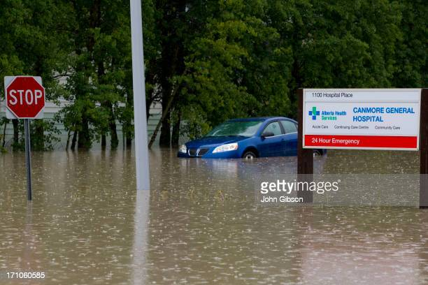A car sits submerged by water outside the Canmore General Hospital due to heavy flooding June 21 2013 in Canmore Alberta Canada Widespread flooding...